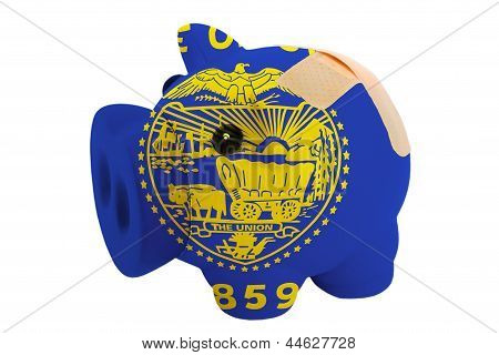 Closed Piggy Rich Bank With Bandage In Colors Flag Of American State Of Oregon