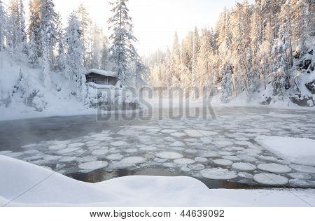 Hut Near Pond In Winter Forest