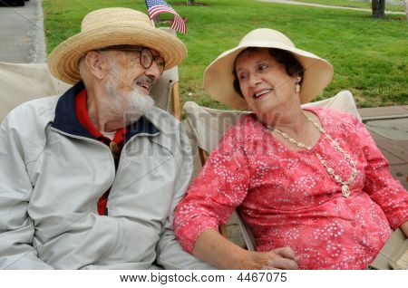 Elderly Couple In Hats Holding Hands, Looking At Each Other, Smiling