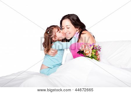 Child Gives Flowers And Kiss To Mom In Bed