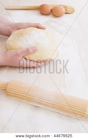 taking the dough with both hands with another tools to knead it