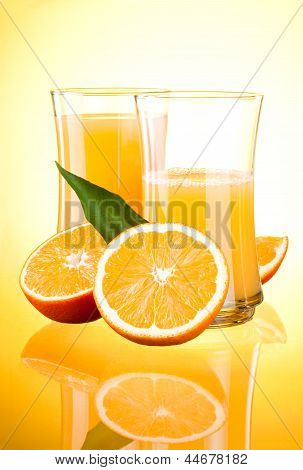 Two Glasses Of Fresh Orange Juice, Half Oranges And The Leaves On Yellow Background