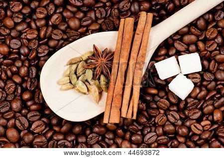 Coffee beans and wooden spoon with spice and lump sugar