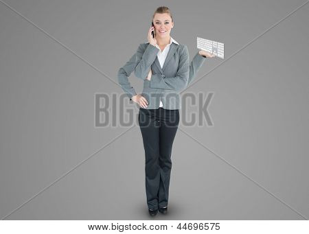 Multi-tasking businesswoman with four arms holding keyboard while on the phone