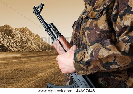 Soldier holding rifle AK-47 against desert