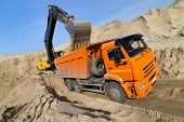 stock photo of dumper  - Yellow Excavator Loading Dumper Truck extreme wide - JPG