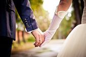 stock photo of floral bouquet  - Closeup of bride and groom holding hands - JPG