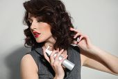 picture of hairspray  - Beautiful girl laying fixes using hairspray  - JPG