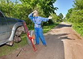 The woman in working overalls tries to replace a wheel at an off-road car, and asks the help..