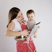 image of multitasking  - Young mother is looking at tablet with her baby