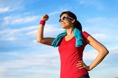 stock photo of fist  - Happy successful fitness woman raising arm with energy and fist to the sky after running and exercising - JPG