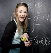 portrait of pretty cute student with book near blackboard