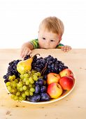 stock photo of snatch  - Baby with dish of fruit on the table - JPG