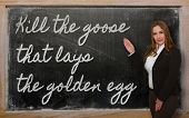 stock photo of laying eggs  - Successful beautiful and confident woman showing Kill the goose that lays the golden egg on blackboard - JPG