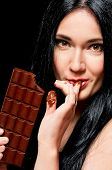 stock photo of finger-licking  - Beautiful young woman with black hair holding a chocolate bar - JPG