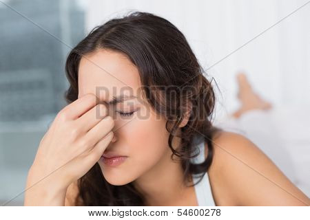 Close-up of a beautiful young woman suffering from headache with eyes closed at home