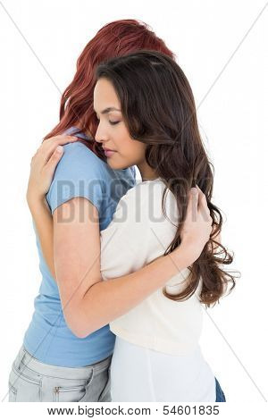 Side view of a young female embracing her friend over white background