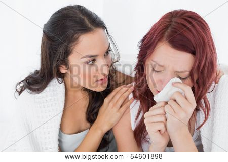 Young woman consoling a crying female friend while sitting on bed at home