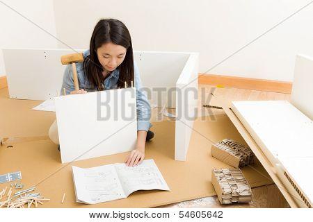 Asian woman inlaying closet using hammer