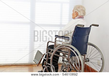 Lonely senior citizen woman in wheelchair in a nursing home