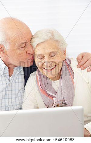 Happy man kissing smiling senior woman at computer