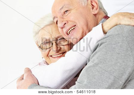Happy senior couple embracing each other and smiling