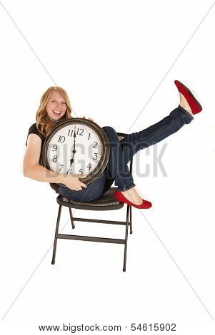Young Woman Holding A Clock In Chair With Enthusiasm