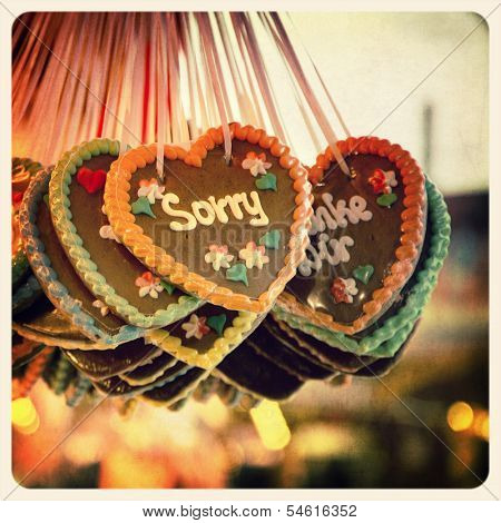 Retro effect image of Gingerbread hearts hanging in a German Christmas market. The prominent heart is iced with the word Sorry. Cross-processed and textured to emulate an old instant photo.