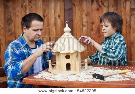 Father and son working on bird house together polishing it with sand paper