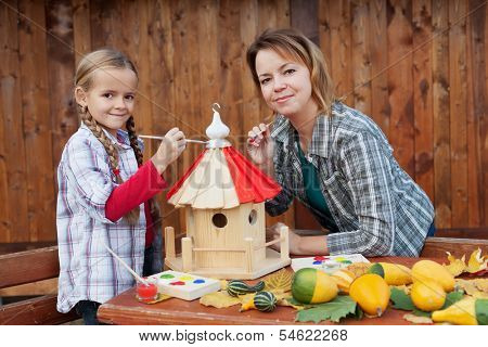 Woman and little girl painting the bird house for winter time