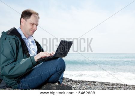 Man With Laptop On Beach