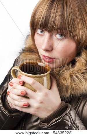 Young girl wearing winter coat heating up with cup of hot tea in cold weather