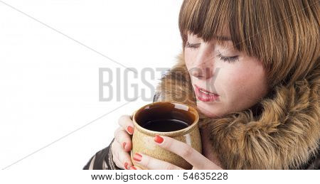 Portrait of young woman holding cup of hot drink to heat up in cold winter