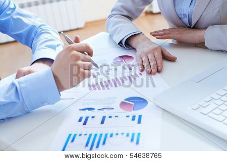 Close-up of male hand pointing at business document in working environment