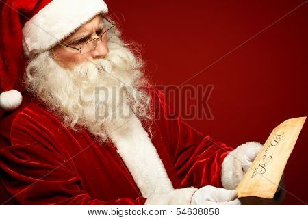 Portrait of Santa Claus looking at Christmas letter in his hands