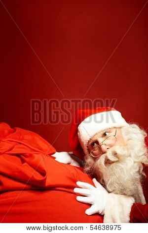 Portrait of Santa Claus leaning over huge red sack