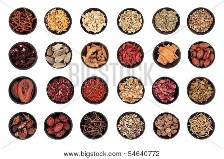 Traditional chinese herbal medicine in wooden bowls isolated over white background.