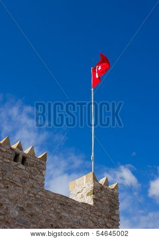 Merlons Of Ancient Fortress With Flag