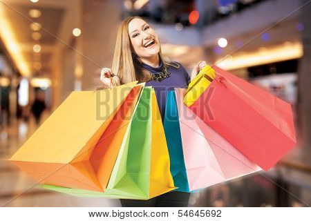 Happy xxl female holds shopping bags. Background digitally added, work path