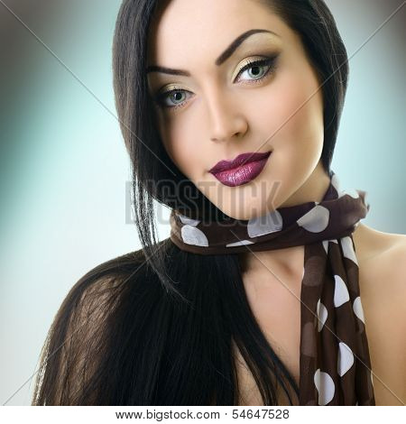 Young attractive woman with nice makeup looking at camera, studio shot of pretty girl