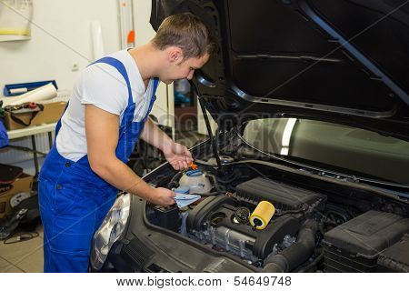 Mechanic In Garage Checking Motor Oil Level At A Car