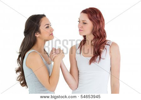 Two casual young female friends arm wrestling against white background
