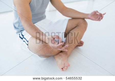 Close-up low section of a young man sitting in lotus pose on the floor