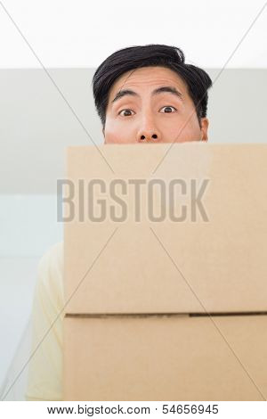 Close-up portrait of a young man carrying boxes in front of his face