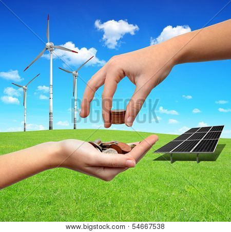 Female hands with money.In the background solar panel and wind turbines