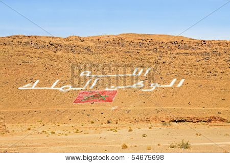 For God, the king and the homeland written on a mountain in Morocco with the moroccan flag