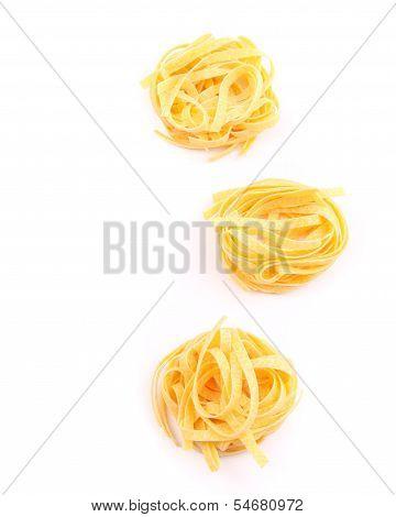 Three fettuccini pasta nests isolated on white.