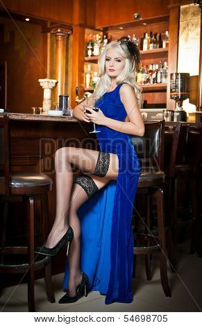 Attractive blonde woman in elegant blue long dress sitting on bar stool holding a glass in her hand.