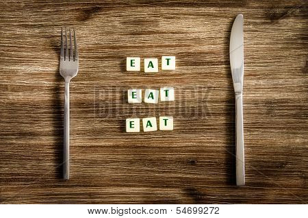 Knife And Fork Set On Wooden Table, Sign Saying Eat