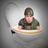 Cowardly soldier hiding in the toilet bowl. Funny picture from army. poster